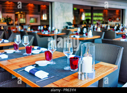 Ascona, Switzerland - August 23, 2016: Typical restaurant terrace with chairs and tables ready for a meal at the luxurious resort in Ascona on Lake Ma - Stock Photo