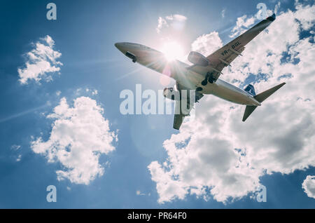 Airplane landing, view from bellow - Stock Photo