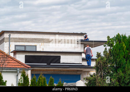 Builders build a house. Workers make a roof on top of the house in work clothes. - Stock Photo