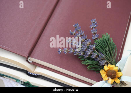 Open cover of book in the top with free space for text decorated with bunch of lavender, dry mini sunflower and green branches