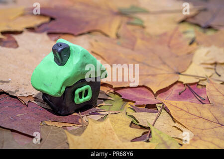 Small house made from Play Clay. Isolated on autumn background. - Stock Photo