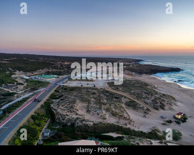 Aerial drone photo of Praia do Guincho beach sand dunes and the coastline at sunset - Stock Photo