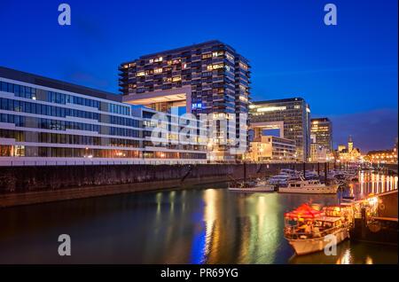 Rheinauhafen water promenade in Cologne Koeln marina at night with boats on the water - Stock Photo