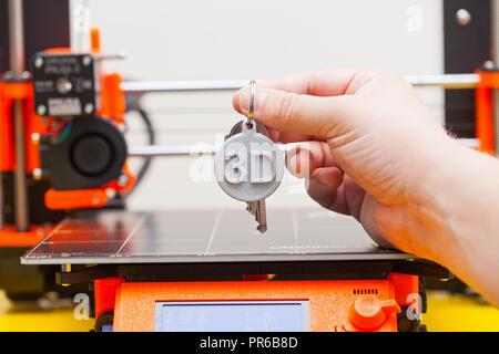 Modern three-dimensional printing. 3D keychain plastic figure in human hand - Stock Photo