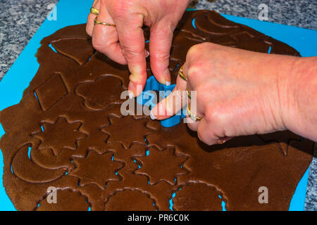 Female hand making the traditional Christmas cookies. Raw dough is being punched out for the holiday cookies on a blue underlay. Preparing gingerbread - Stock Photo