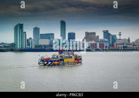 Mersey ferry Snowdrop, painted with Sir Peter Blake's Everybody Razzle Dazzle design, sails from Birkenhead towards Liverpool  Pier Head. - Stock Photo