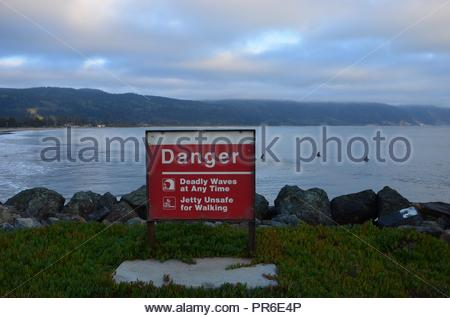 Evening in Crescent City in Del Norte County in California, Pacific Coast, September, surfer on a wave, harbor - Stock Photo