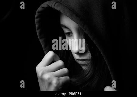 scared girl in hood looking down on black background, monochrome - Stock Photo