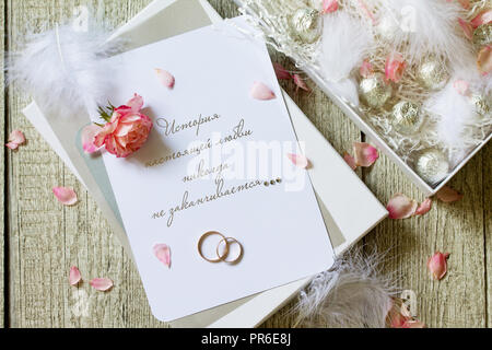 Two Golden Wedding Rings, box of chocolates and a wedding invitation, an inscription that the story of true love never ends. Top view flat lay backgro - Stock Photo