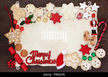 Merry Christmas background border with sign, tree decorations, biscuits, cakes, winter flora  and chocolates in foil on parchment paper on rustic wood - Stock Photo