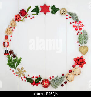 Abstract Christmas wreath garland with a selection of traditional symbols including food, flora and bauble decorations on rustic white wood background - Stock Photo