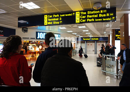 People waiting for people at the Arrival Hall at Manchester International Airport, UK - Stock Photo