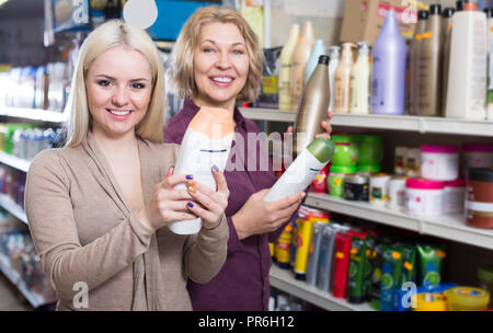 mother and adult daughter in good spirits selecting shampoo in the supermarket - Stock Photo