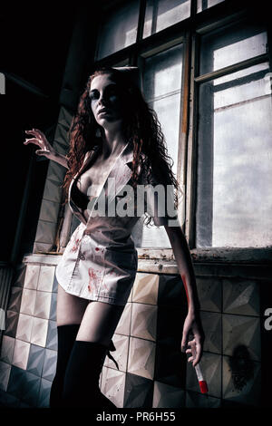 Horror shot: the creepy evil mad nurse (doctor) with bloody syringe in hand. Zombie woman (living dead) - Stock Photo