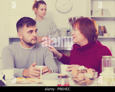 Elderly mother comforting her son after discord with wife at home - Stock Photo