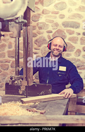 Succesful professional woodworker on lathe at musical instrument workroom - Stock Photo