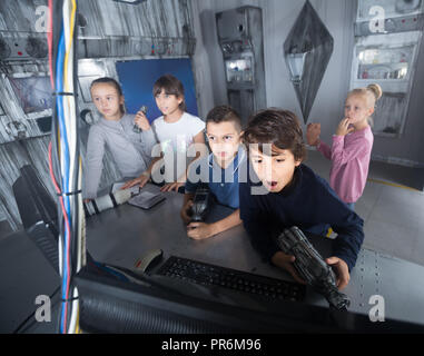 Enthusiastic french children play in the quest room of a inscrutable bunker - Stock Photo