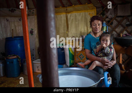 A little girl seen in the arms of her grand mother next to the milk cooking pot inside their yurt near the small town of Adaatsag in the Dundgovi Province in Central Mongolia. - Stock Photo