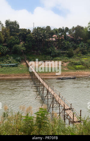 View of a bamboo bridge over Nam Khan River and lush riverbank in Luang Prabang, Laos, on a sunny day. - Stock Photo
