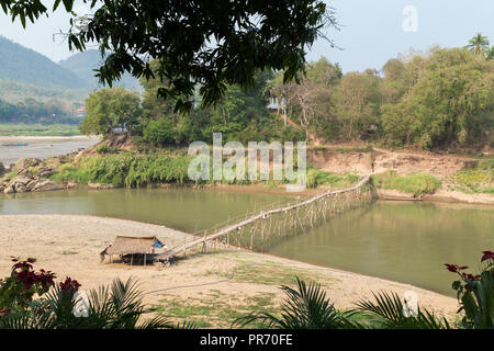 View of a bamboo bridge over Nam Khan River at low tide and lush riverbank in Luang Prabang, Laos, on a sunny day. - Stock Photo