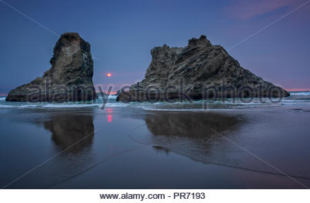Sea stacks reflected in the water at sunset on a beach in Bandon, Oregon - Stock Photo