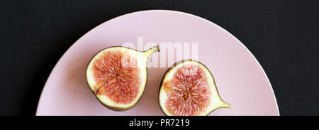 Two halves of fresh fig on pink plate on black table, top view. Flat lay, overhead, top view. - Stock Photo