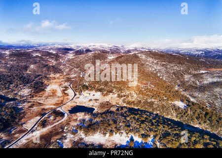 Distant mountains peaks covered by white snow in winter season high in Snowy mountains of australia - popular skiing and snowboarding resort of Perish - Stock Photo