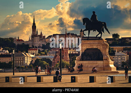 Sunset city skyline of Budapest. Matthias Church, Fisherman's Bastion and other historical buildings on Castle Hill with statue of Gyula Andrassy. - Stock Photo