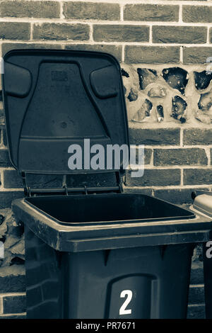 Black and white close up of a wheelie bin next to a brick and flint wall - Stock Photo