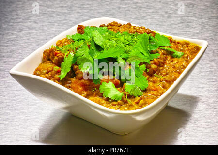 Moong Dahl, indian vegetarian lentil soup, in white bowl. Aluminium background. - Stock Photo