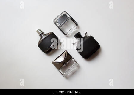 Four glass perfume bottles isolated on white background from a high angle view - Stock Photo
