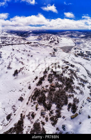 Regional remote village of Perisher valley high in Snowy Mountains of Australia during winter skiing season with lots of snow on slopes of the resort. - Stock Photo