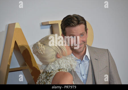 Lady Gaga kisses Bradley Cooper, at the London film premier of A Star is Born. - Stock Photo