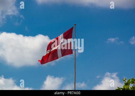 Danish flag on a sunny day with a clear blue sky - Stock Photo