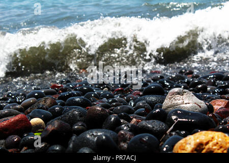 Beach colorful rocks and a wave in background - Stock Photo