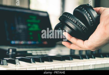 Sound engineer holding Studio headphone in home studio - Stock Photo