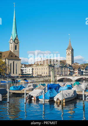 Zurich, Switzerland - November 25, 2013: boats at a pier on the Limmat river, buildings of the historic part of the city in the background. Zurich is  - Stock Photo