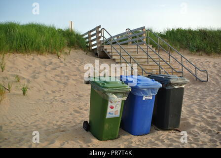 Recycle, waste and organics disposal bins in three colours green, blue and black on a red sandy beach, enrance, Greenwich National Park, PEI. Canada - Stock Photo