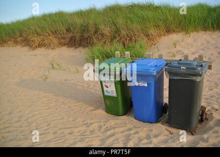 Recycle, waste and organics disposal bins in three colours green, blue and black on a red sandy beach at Greenwich National Park, PEI. Canada - Stock Photo