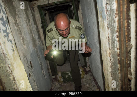 18 September 2018, Saxony-Anhalt, Colbitz: Holger Wille, Head of the Lindenwald district, ducks down on the Altmark military training area in the Letzlinger Heide near Colbitz and walks through a former Soviet bunker. There is a bat quarter which was established as a compensatory measure for the construction of the A14 motorway. Photo: Klaus-Dietmar Gabbert/dpa-Zentralbild/dpa - Stock Photo