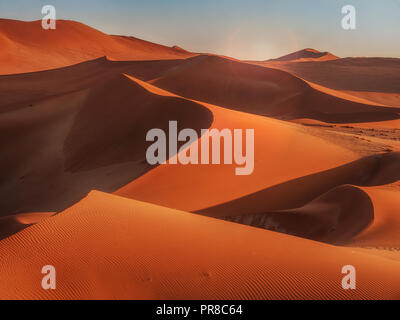 Sun rising over the curves, lines, and shadows of the red sand dunes of Namib Desert, Namibia. - Stock Photo