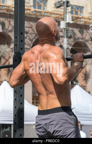 Athlete muscular fitness male model pulling up on horizontal bar in a gym. Closeup of strong athlete doing pull-up on horizontal bar. vertical photo. - Stock Photo