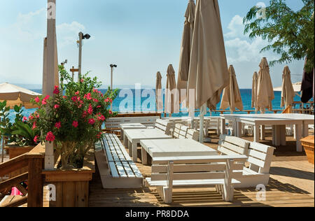 white tables and benches against the sea - Stock Photo