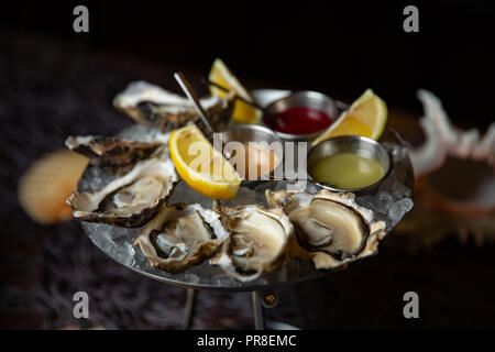 Oysters plate with lemon on dark background Served table with oysters and lemon. Fresh oysters close-up top view. Healthy sea food. Oyster dinner in r - Stock Photo