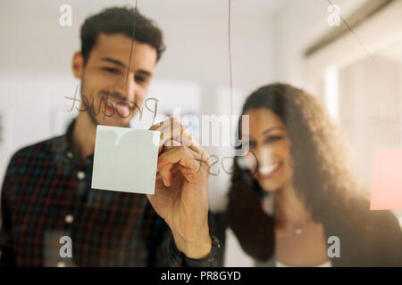 Business couple writing on sticky notes pasted on transparent glass wall in office. Office colleagues discussing business ideas and plans on a transpa - Stock Photo