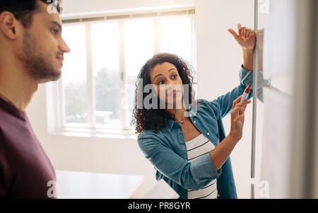 Woman entrepreneur discussing business ideas and plans on a board in office. Businesswoman writing on a whiteboard and explaining while her colleague  - Stock Photo