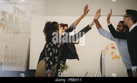 Business colleagues giving high five to each other standing in office. Team members celebrating success at work by giving high five. - Stock Photo