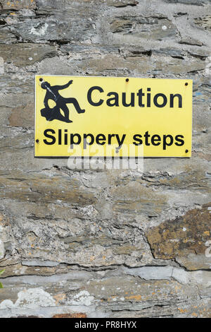 Slippery steps warning sign. Harbour scenes around Newquay, Cornwall - Stock Photo