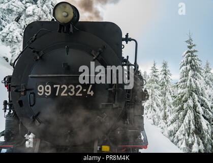 Harzer Brockenbahn Narrow gauge engine from the front while driving in sowy landscape - Stock Photo