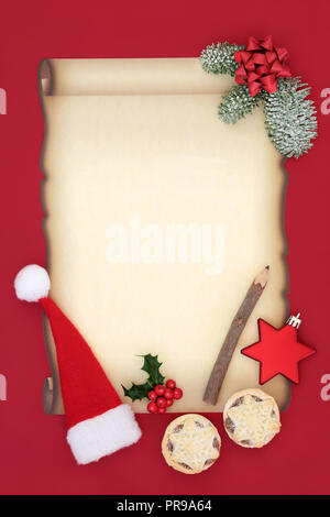 Letter to Father Christmas or invitation with blank parchment paper, santa hat, mince pies, pencil, bow, star bauble and winter flora on red. - Stock Photo